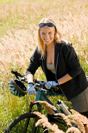 Mountain biking happy young woman relax in cornfield sunny countryside photo