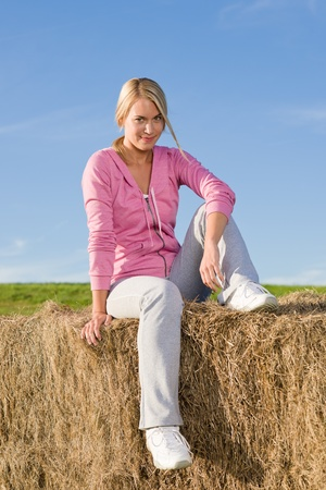 Portrait of sportive young woman relax sitting on hay bales photo