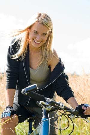 woman bike: Mountain biking happy young woman relax in cornfield sunny countryside Stock Photo