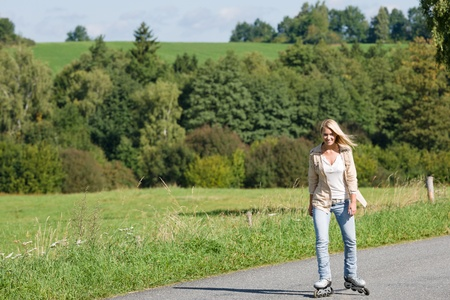 Inline skating young woman wearing jeans on sunny asphalt road photo
