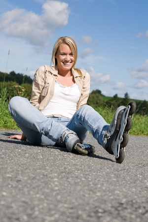 rollerskating: Inline skates young attractive woman wearing jeans sitting asphalt road
