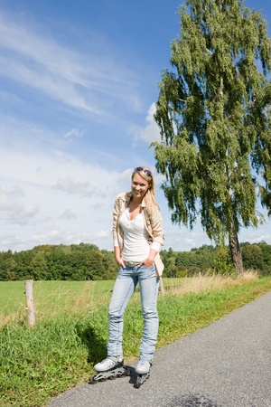 inline skating: Inline skating young woman wearing jeans on sunny asphalt road Stock Photo