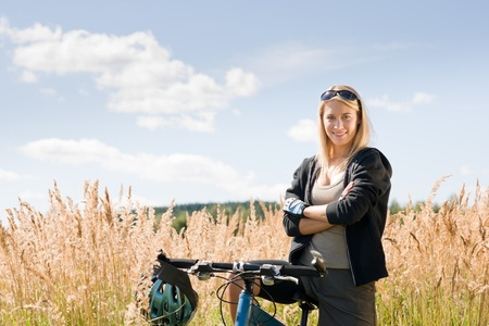 cycling helmet: Mountain biking happy young woman relax in cornfield sunny countryside Stock Photo