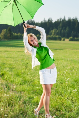 Happy young woman with green umbrella in sunny meadows nature photo