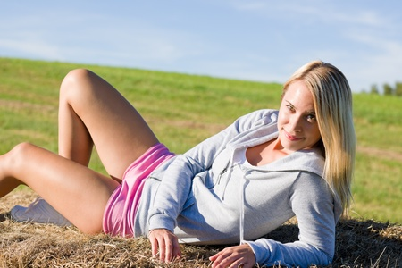 Portrait of sportive young woman relax on hay bales