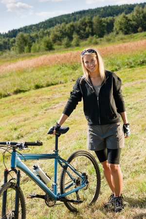 Mountain biking happy sportive girl relax in meadows sunny countryside photo
