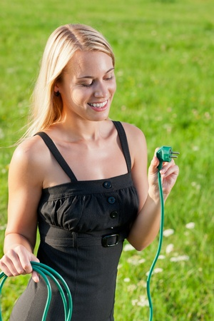Green energy - young attractive businesswoman hold plug green sunny meadows photo