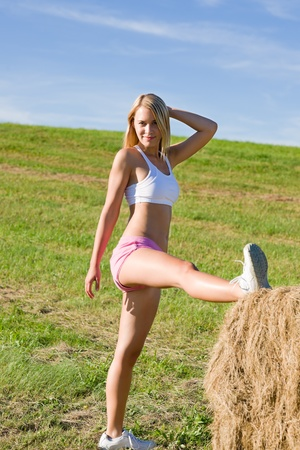 sportive: Summer active woman stretching on bales in fitness outfit Stock Photo