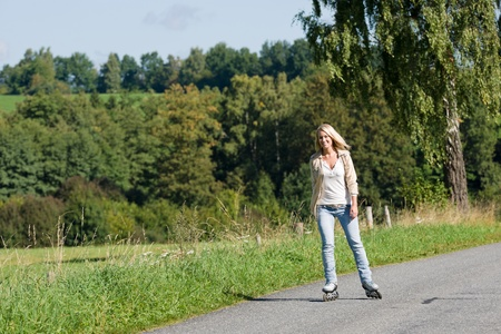 rollerblading: Inline skating young woman wearing jeans on sunny asphalt road Stock Photo
