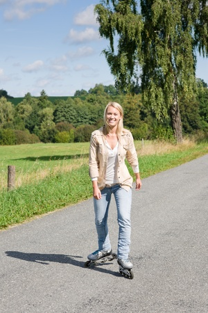 rollerskating: Inline skating young woman wearing jeans on sunny asphalt road Stock Photo