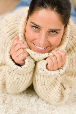 Winter portrait of happy woman wear pollover smiling lying floor photo