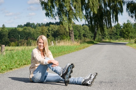 rollerblading: Inline skates young attractive woman wearing jeans sitting asphalt road