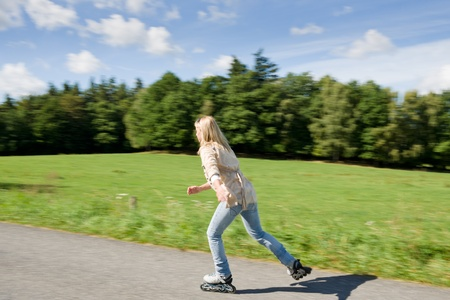 rollerblade: Inline skating young woman speed workout sunny asphalt road