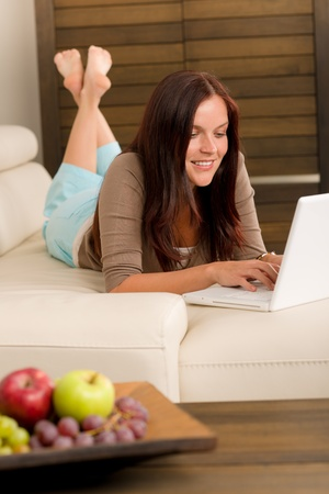 Attractive woman with laptop lying modern leather sofa living room Stock Photo - 10767372