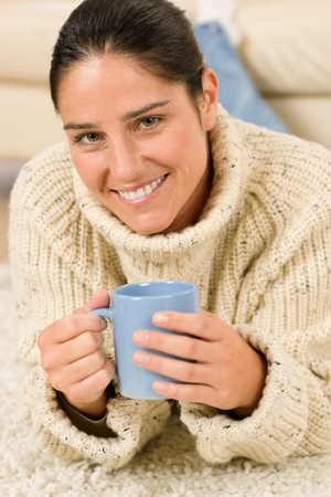 Happy woman with coffee cup wear pullover on white background photo