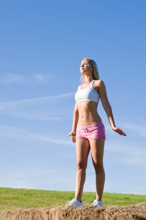 Summer active woman stretching on bales in fitness outfit Stock Photo - 10795304