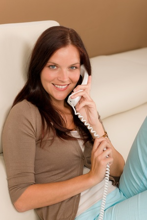 calling on phone: Home attractive smiling woman calling phone in living room