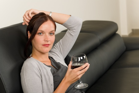 Elegant businesswoman sitting on leather sofa drink glass red wine photo