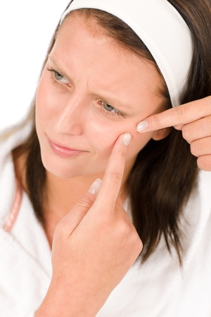 Acne facial care teenager woman squeezing pimple on white photo