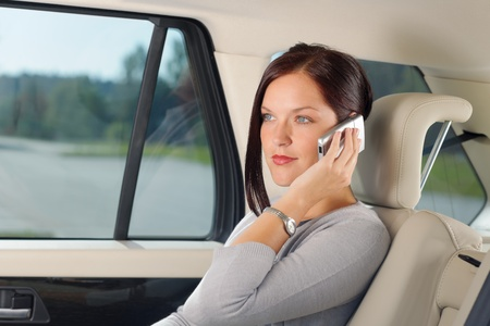 Executive attractive female manager sitting in car backseat calling phone photo