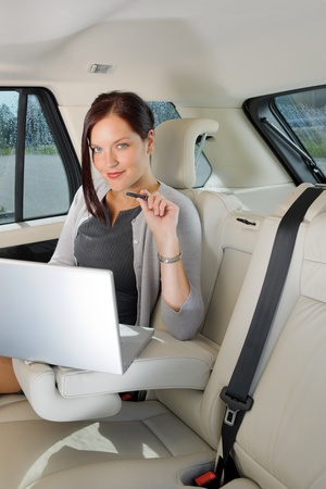 Executive woman manager working on laptop sitting car leather backseat