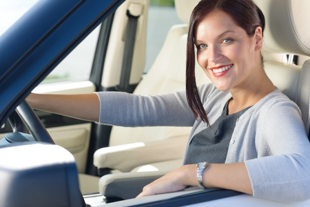 Attractive elegant businesswoman driving luxury car smiling at camera Stock Photo - 10879570