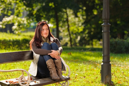 mujer sentada: La moda de otoño mujer ropa atractiva puesta de sol sentado en banco de un parque