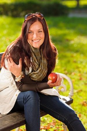 Autumn fashion smiling beautiful woman eat apple sunset nature park photo