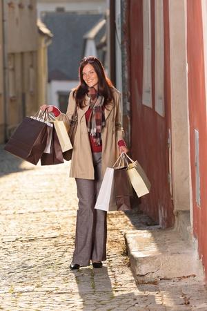 Fall elegant woman carrying shopping bags walking city street sunset photo