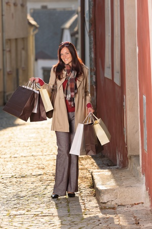 Fall elegant woman carrying shopping bags walking city street sunset photo