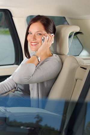 happy rich woman: Executive attractive female manager sitting in car backseat calling phone