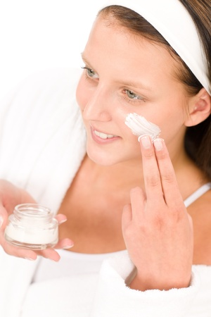 Acne facial care teenager woman apply cream foam on white photo