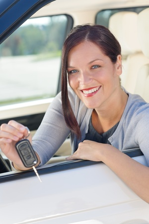 Attractive elegant businesswoman in new car showing keys smiling photo