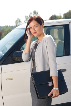 Attractive elegant business woman near luxury car hold briefcase calling photo