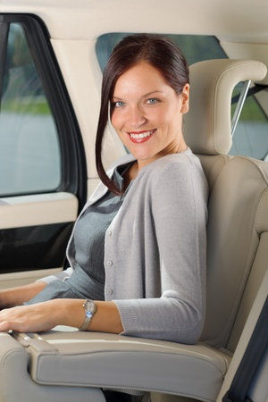 Executive businesswoman sitting in car leather backseat wear suit photo