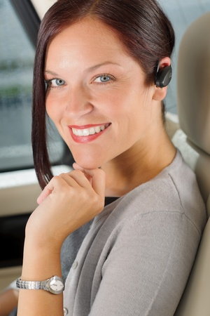 sexy woman car: Attractive executive female manager sitting in car backseat calling hands-free Stock Photo