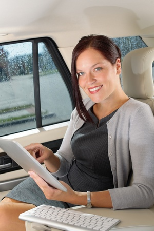 Attractive executive female manager work luxury car touch tablet computer photo