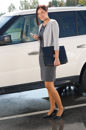 sexy woman car: Attractive elegant business woman near luxury car hold briefcase calling
