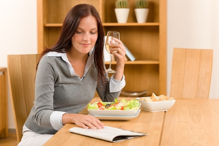 Healthy lunch at home attractive woman read magazine drink wine photo