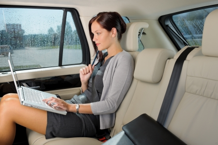 businesswoman: Executive woman manager working on laptop sitting car leather backseat