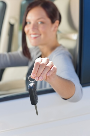 Attractive elegant businesswoman in new car showing keys smiling Stock Photo - 10879648