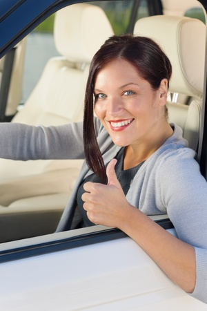 Attractive elegant businesswoman driving luxury new car thumb up smiling photo