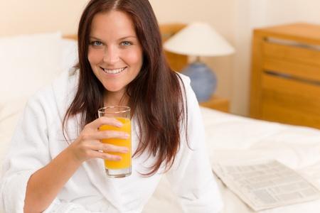 Breakfast - Smiling woman with fresh orange juice in white bedroom photo