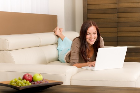 Attractive woman with laptop lying modern leather sofa living room photo