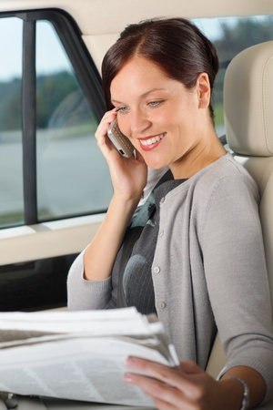 Attractive executive businesswoman sitting in car calling phone checking newspapers photo