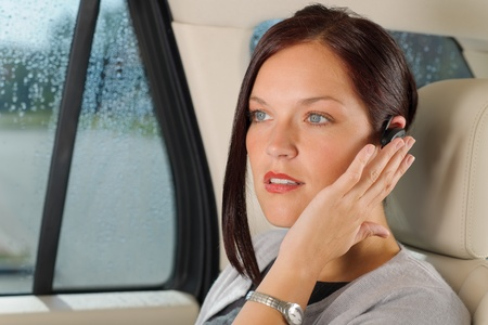Attractive executive female manager sitting in car backseat calling hands-free photo