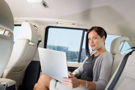 Executive woman manager working on laptop sitting car leather backseat photo