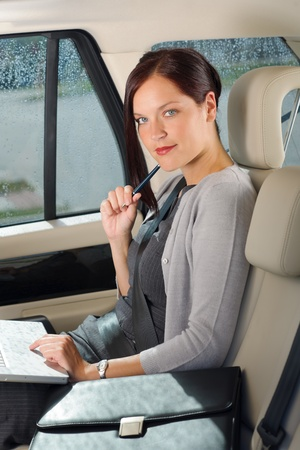 Executive woman manager working on laptop sitting car leather backseat photo