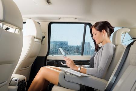 passenger vehicle: Atractivo ejecutivo de obra femenina gerente de autom�viles de lujo touch tablet PC Foto de archivo
