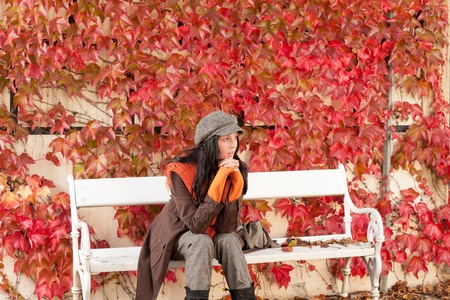sitting on a bench: Autumn leaves park scenery young woman relax sitting on bench Stock Photo